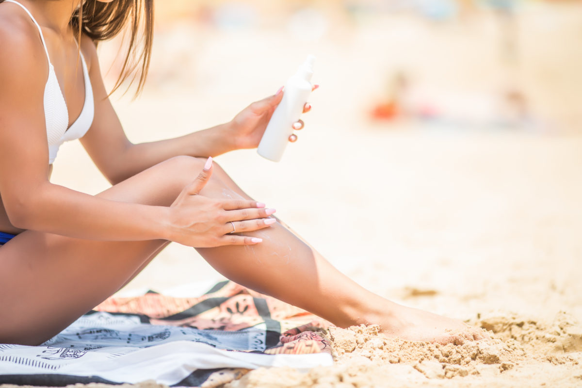 sunscreen-suntan-lotion-in-spray-bottle-young-woman-in-spraying-tanning-oil-on-her-leg-from-bottle-lady-is-massaging-sunscreen-lotion-while-sunbathing-at-beach-female-model-during-summer-vacation-1200x800.jpg